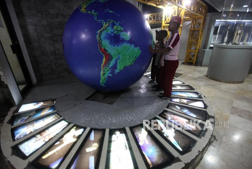 Sejumlah siswa Sekolah Dasar Peninggalan 04 Ciledug Tangerang (SD) mengamati alat peraga tata surya saat berkunjung ke Planetarium Jakarta, Kamis (8/11).