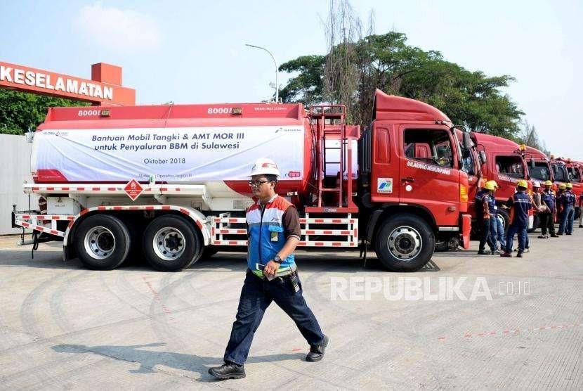 Petugas melintas didekat mobil tangki yang akan mendistribusikan BBM dan Avtur menuju ke Sulawesi, di Terminal Bahan Bakar Minyak (TBBM) Plumpang, Jakarta, Selasa (2/10).