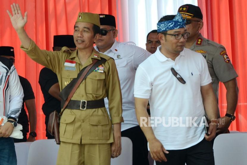 Presiden RI Joko Widodo (Jokowi) menggunakan kostum pejuang didampingi Gubernur Jawa Barat Ridwan Kamil (kedua kanan) melambaikan tangan saat hadir pada acara Bandung Lautan Sepeda dalam rangka Hari Pahlawan, di kawasan Gasibu, Kota Bandung, Sabtu (10/11).