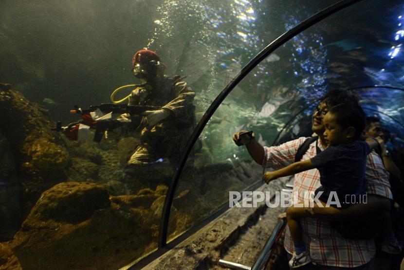 Pengunjung melihat penyelam tampil di dalam air (underwater) dalam rangka memperingati hari kemerdekaan Indonesia yang ke-74 di Seaworld, Ancol, Jakarta, Sabtu  (17/8).