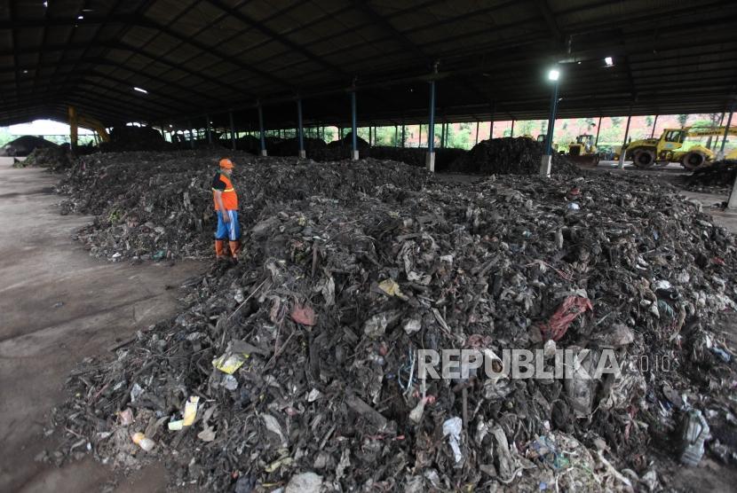 Seorang petugas mengecek tumpukan sampah yang akan diolah dengan fasilitas mesin pengomposan di Tempat Pengelolaan Sampah Terpadu (TPST) Bantargebang, Bekasi, Jawa Barat, Rabu (21/3).