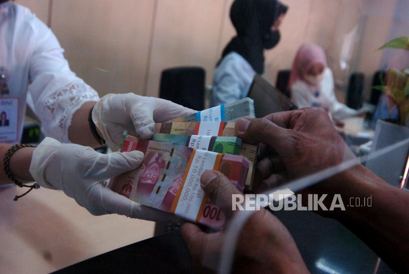 Petugas melakukan transaksi dengan nasabah saat penukaran uang.