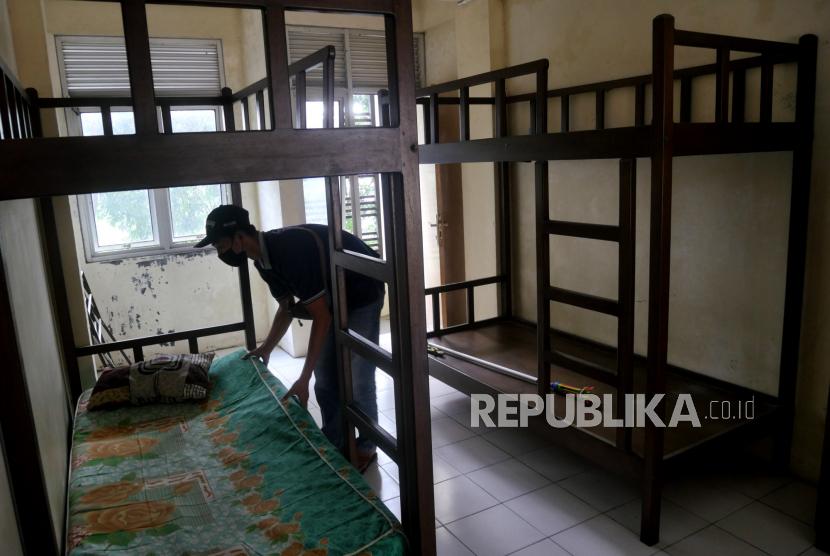 Petugas memeriksa tempat tidur di salah satu shelter isolasi Covid-19.