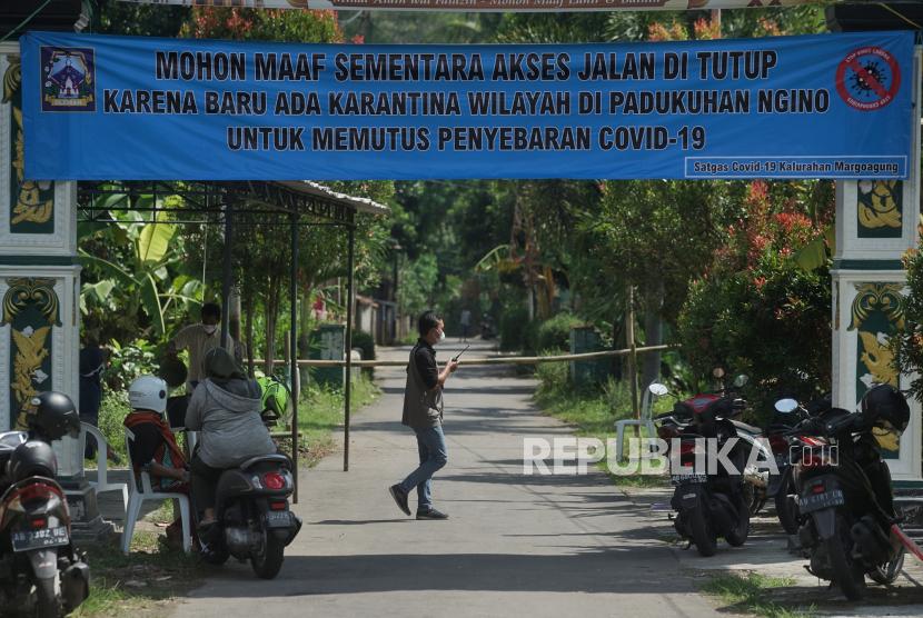 Petugas berjaga di pintu masuk kampung saat karantina wilayah di Padukuhan Ngino XII, Margoagung Sleman, D.I Yogyakarta, Jumat (18/6/2021). Sejak 16 Juni 2021, Padukuhan Ngino XII dan Ngino XI melakukan karantina wilayah guna memutus penyebaran COVID-19 menyusul sejumlah warga di kampung itu terpapar COVID-19 seusai melakukan ziarah.
