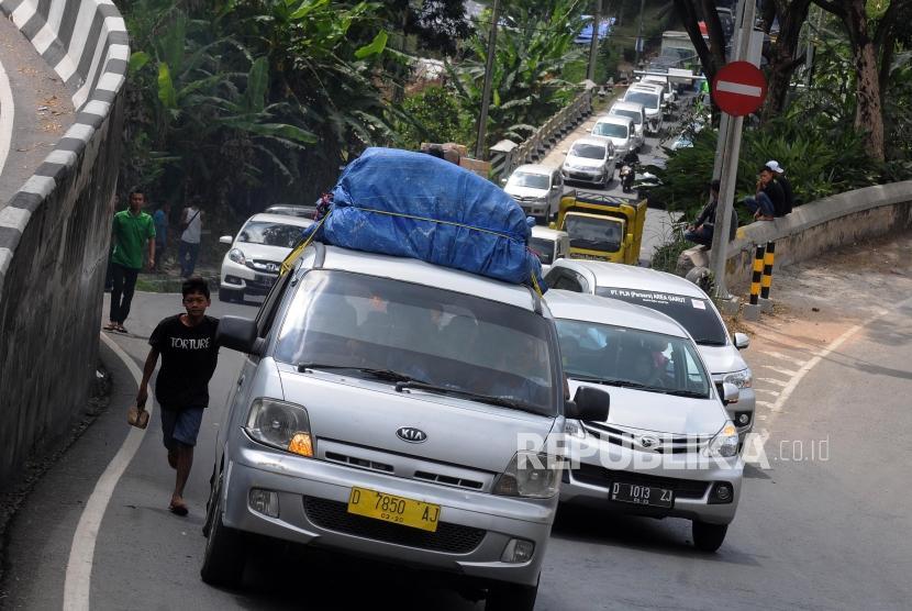 Warga usai mengganjal ban mobil pemudik di kawasan Nagreg, Kabupaten Bandung, Jawa Barat, Rabu (13/6).
