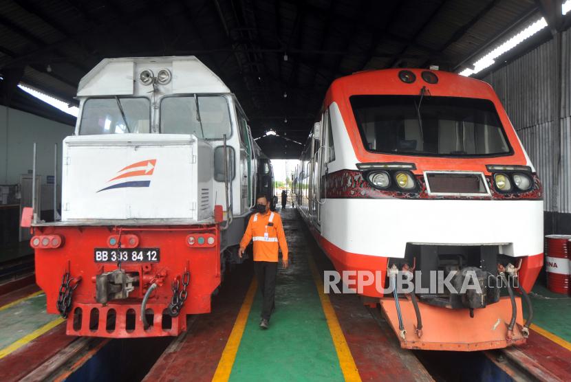 Petugas PT Kereta Api Indonesia melintas depan kereta api yang dibersihkan, di Depo Stasiun Simpang Haru, Padang, Sumatera Barat, Sabtu (25/4/2020). PT KAI  Divre II Sumbar membatalkan seluruh keberangkatan dan kedatangan perjalanan Kereta Api penumpang mulai 25 April 2020 hingga waktu yang belum ditentukan, dalam rangka mendukung kebijakan pemerintah tentang larangan mudik lebaran mencegah penyebaran COVID-19