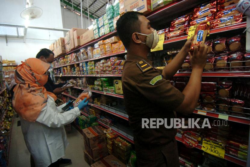 Petugas memeriksa tanggal kadaluarsa makanan saat razia makanan minuman di salah satu tempat perbelanjaan.