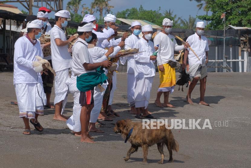 Umat Hindu melakukan upacara Mapekelam saat pelaksanaan Pemberlakuan Pembatasan Kegiatan Masyarakat (PPKM) Level 4 di Pantai Batu Bolong, Badung, Bali, Selasa (27/7/2021). Berdasarkan Surat Edaran Gubernur Bali Nomor 12 Tahun 2021 tentang Pemberlakuan Pembatasan Kegiatan Masyarakat (PPKM) Level 4 dalam tatanan kehidupan era baru di Provinsi Bali yang berlaku pada 26 Juli 2021 hingga 2 Agustus 2021 tersebut memberlakukan ketentuan mengenai kegiatan keagamaan dilaksanakan dengan melibatkan jumlah orang yang sangat terbatas dan menerapkan protokol kesehatan serta atas seizin Satgas COVID-19 Kabupaten/Kota.