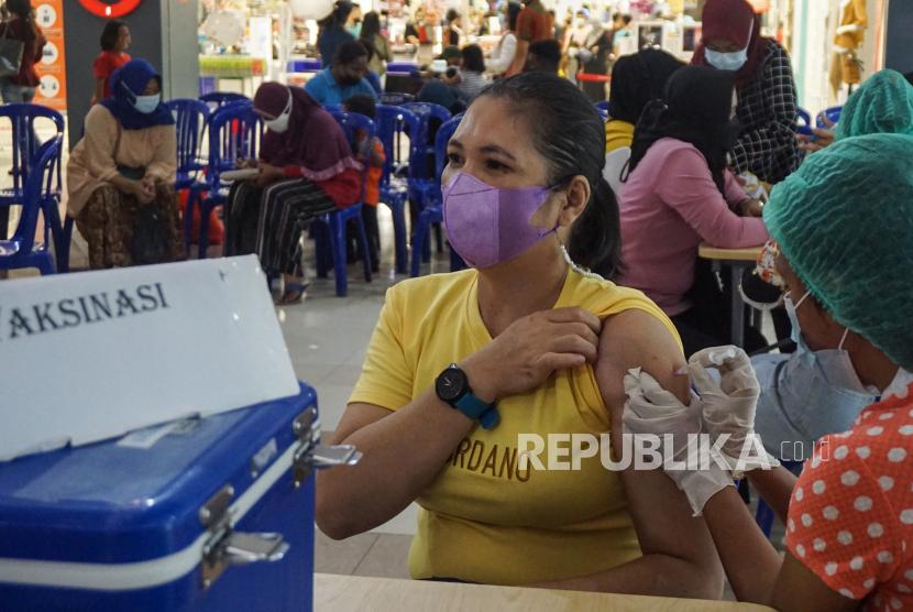 Petugas kesehatan menyuntikkan vaksin COVID-19 ke warga di koridor Mall Kota Jayapura, Papua, Ahad (19/9/2021). Polresta Jayapura Kota bersama relawan vaksinator Universitas Cenderawasih (Uncen) dan Poltekes Jayapura melakukan vaksinasi di sejumlah titik pusat keramaian untuk mendukung program tercapainya target sebanyak 70 persen warga Papua telah divaksin sebelum PON Papua.