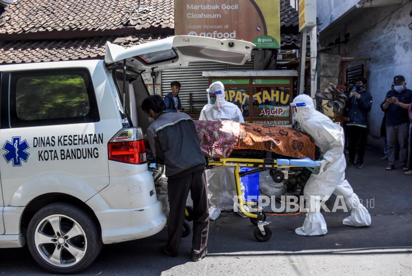 Petugas Public Safety Center 119 (PSC 119) bersama warga mengevakuasi jenazah pasien Covid-19 yang meninggal saat isolasi mandiri (isoman) di rumahnya di Jalan Padasuka, Cibeunying Kidul, Kota Bandung, Rabu (28/7). Berdasarkan hasil data yang dihimpun dari situs laporcovid19.org hingga (28/7) tercatat kasus kematian pasien Covid-19 saat isolasi mandiri dan di luar rumah sakit mencapai 2.705 kasus.