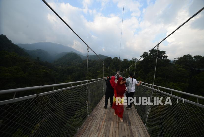 Wisatawan  melintasi  Situ Gunung Suspension Bridge di Taman Nasional Gunung Gede Pangrango, Kadudampit, Sukabumi, Selasa (19/6).