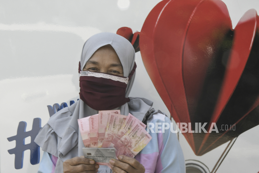 Warga menunjukkan uang BLT (Bantuan Langsung Tunai) dana desa di Setu, Kabupaten Bekasi, Jawa Barat, Rabu (28/7/2021). Kementerian Keuangan mencatat realisasi BLT Dana Desa baru 21,3% karena pemerintah daerah melakukan verifikasi ulang data penerima warga yang terdampak pandemi COVID-19.