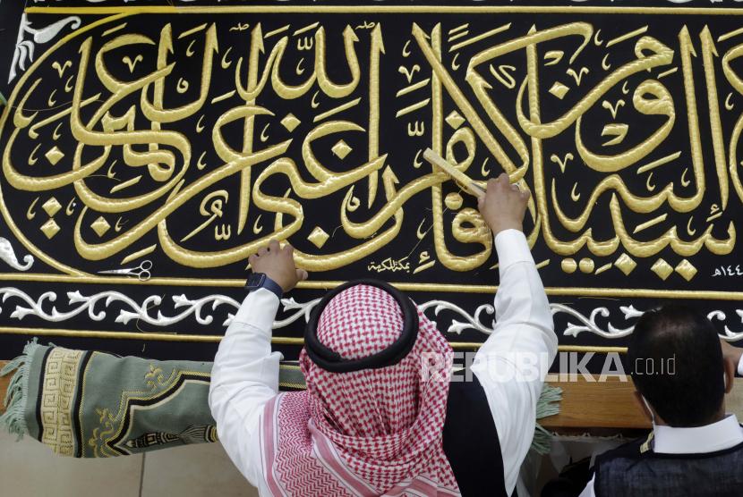 Seorang pria Saudi menyulam kaligrafi Islam, baik menggunakan benang perak murni atau benang perak berlapis emas, selama tahap akhir dalam persiapan tirai, atau Kiswah, yang menutupi Ka