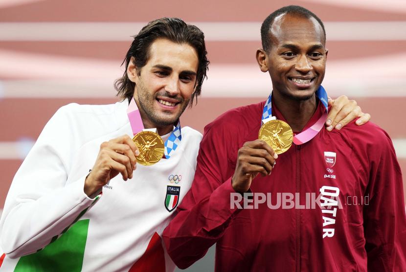 Peraih medali emas gabungan Mutaz Essa Barshim (kanan) dari Qatar dan Gianmarco Tamberi (kiri) dari Italia saat upacara medali untuk Lompat Tinggi Putra di cabang Atletik Olimpiade Tokyo 2020 di Stadion Olimpiade di Tokyo, Jepang, 02 Agustus 2021 .