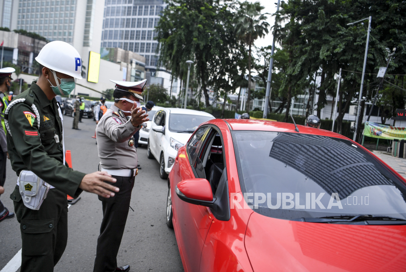 Polisi mengimbau pengendara mobil saat pemeriksaan kepatuhan Pembatasan Sosial Berskala Besar (PSBB) di kawasan Bundaran HI, Jakarta, Senin (13/4/2020). Pemeriksaan tersebut untuk memastikan setiap pengendara mobil dan motor mematuhi aturan PSBB yang diterapkan di DKI Jakarta