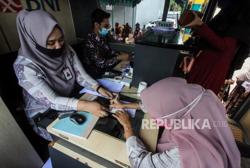 Guru honorer meneken dokumen buku tabungan bank BNI saat pencairan bantuan subsidi upah (BSU) di Lhokseumawe, Aceh, Kamis (26/11/2020). Kementerian Pendidikan dan Kebudayaan (Kemendikbud) menetapkan 2.034.732 orang terdiri guru, Dosen, Tenaga perpustakaan, Tenaga laboratorium, dan tenaga administrasi sebagai penerima BSU sebesar Rp1,8 juta dengan total anggaran Rp 3,6 triliun bersumber APBN 2020.