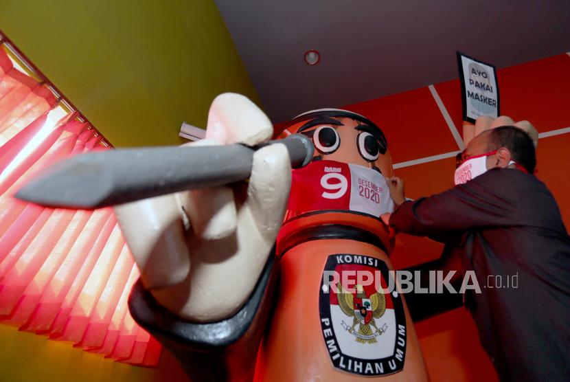 Ketua KPU Kota Blitar Choirul Umam memasangkan masker bertuliskan Rabu 9 Desember 2020 pada maskot Pilwakot Blitar Si Kendang Memilih (Sidanglih) saat peluncuran tahapan Pilkada serentak di Kantor KPU Kota Blitar, Jawa Timur, Senin (15/6/2020). Kementerian Dalam Negeri (Kemendagri) mengubah ketentuan pencairan belanja hibah kegiatan pemilihan yang dilakukan secara bertahap menjadi dua tahap saja.