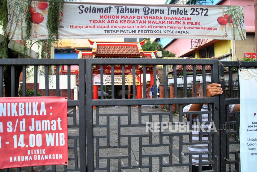 Penjaga vihara menutup pintu gerbang Vihara Dhanagun, Kota Bogor, Jawa Barat, Senin (8/2/2021). Pengurus Vihara Dhanagun, Bogor tidak mengadakan kegiatan ibadah jemaat pada malam dan Tahun Baru Imlek 2572 dan menghimbau umat untuk merayakannya di rumah masing-masing bersama keluarga sebagai upaya menekan tingginya angka kasus positif COVID-19 di Kota Bogor.