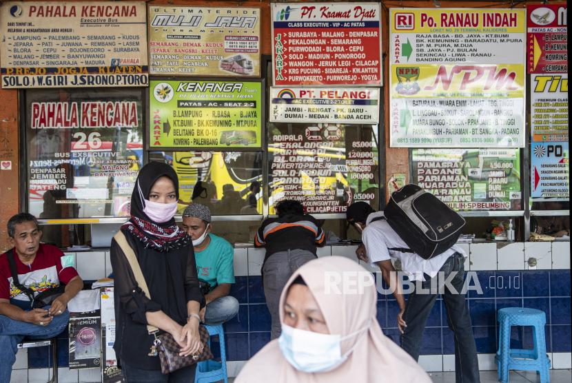 Sejumlah calon penumpang dengan mengenakan masker menunggu di depan loket, Terminal Kalideres, Jakarta Barat, Senin (26/4/2021). Meski adanya aturan larangan mudik mulai dari 22 April - 24 Mei 2021, armada perusahaan otobus (PO) tetap beroperasi di Terminal Kalideres.