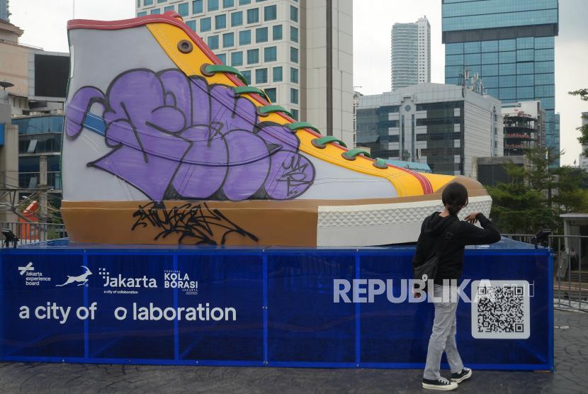 Warga mengamati vandalisme di Tugu Sepatu di kawasan Stasiun BNI City, Jakarta, Ahad (19/9). Tugu Sepatu yang baru diresmikan pada Jumat (17/9) kemarin ini menjadi sasaran vandalisme sejumlah oknum. Akibat aksi tersebut Pemprov DKI Jakarta akan segera menindak lanjuti aksi vandal tersebut. Republika/Thoudy Badai