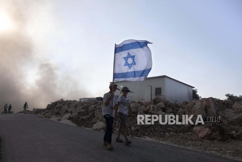 Pemuda Israel membawa bendera di pos terdepan Eviatar dekat kota Nablus di Tepi Barat utara, Senin, 21 Juni 2021. Israel menetapkan enam kelompok masyarakat sipil Palestina sebagai organisasi teroris.
