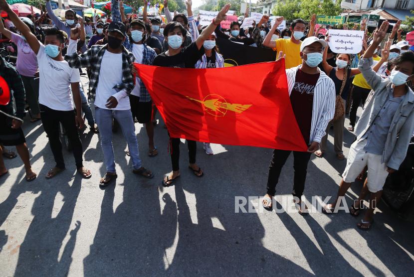 Para pengunjuk rasa memberi hormat tiga jari saat mereka membawa bendera serikat mahasiswa selama protes terhadap kudeta militer di Mandalay, Myanmar, 21 Mei 2021.