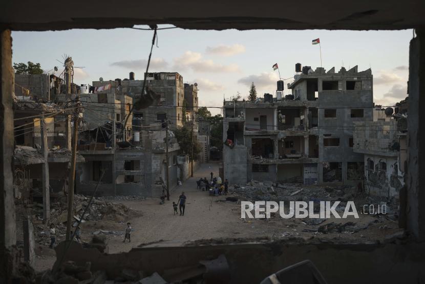 Bendera Palestina berkibar di atas gedung-gedung yang rusak berat akibat serangan udara selama perang 11 hari antara penguasa Hamas Gaza dan Israel, Sabtu, 5 Juni 2021, di Beit Hanoun, Jalur Gaza.