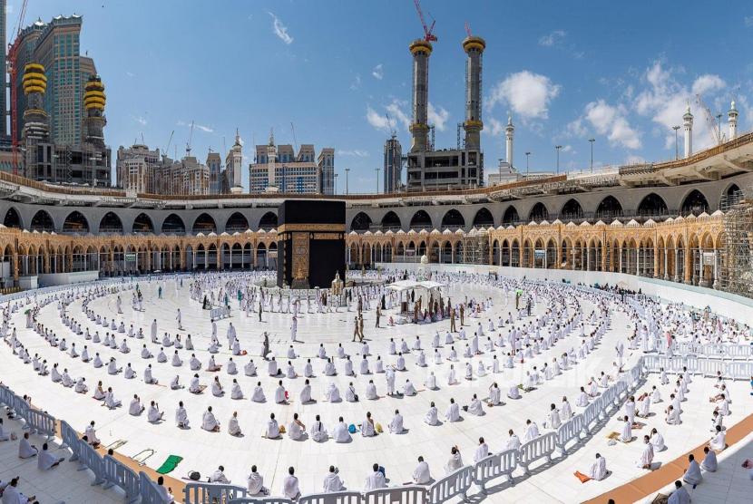 Arab Saudi Umumkan Tiga Paket Biaya Haji Mulai Rp 46 Juta. Umat Muslim, yang menjaga jarak, melakukan sholat Jumat saat mereka tiba untuk menunaikan Umrah, di Masjidil Haram, di kota suci Mekkah, Arab Saudi, 26 Februari 2021.