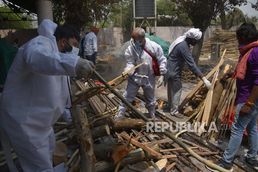 Anggota keluarga mengumpulkan kayu bakar untuk kremasi di tempat kremasi di New Delhi, India, Kamis (29/4). Delhi melaporkan 25.986 kasus baru, 368 kematian dalam 24 jam terakhir dan terus berjuang dengan pasokan oksigen.