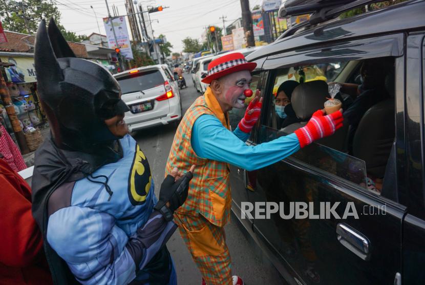 Warga berkostum badut membagi takjil kepada pengguna jalan di Pekalongan, Jawa Tengah, Ahad (18/4/2021). Batik Magic Clown, Cospek dan komunitas lainnnya berkolaborasi membagikan 1.000 takjil kepada warga pengguna jalan jelang waktu berbuka puasa untuk memupuk rasa saling berbagi di bulan suci Ramadhan.
