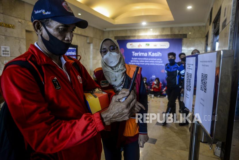 Atlet DKI Jakarta memindai kode batang sebelum menjalani karantina di Hotel Grand Cempaka Business, Jakarta, Kamis (14/10). Pemerintah Provinsi DKI Jakarta telah menyiapkan dua fasilitas isolasi terpusat di Hotel Grand Cempaka Business dan D