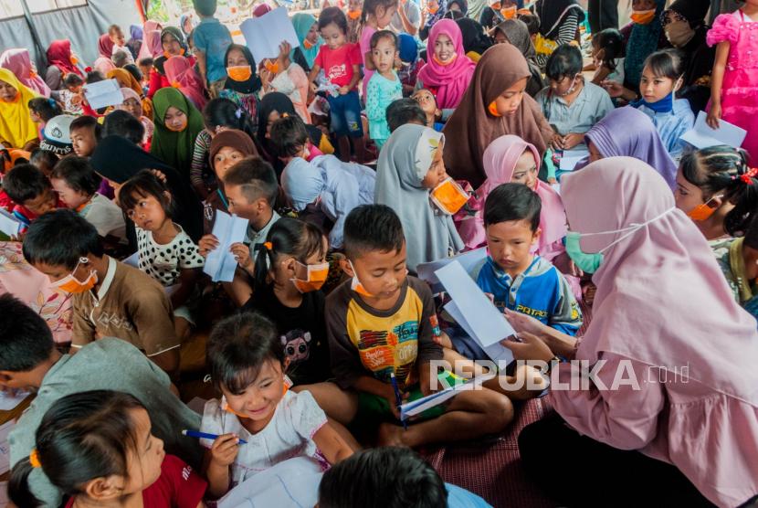 Sejumlah relawan Perlindungan Anak Terpadu Berbasis Masyarakat (PATBM) bermain dan menghibur bersama anak-anak pengungsi korban longsor di Kampung Cigobang, Lebak, Banten, Kamis (9/7/2020). Kegiatan tersebut guna memberikan dukungan psikososial melalui berbagai aktivitas kegiatan hiburan untuk anak-anak pengungsi korban bencana longsor. ANTARA FOTO/Muhamamad Bagus Khoirunas/agr/nz