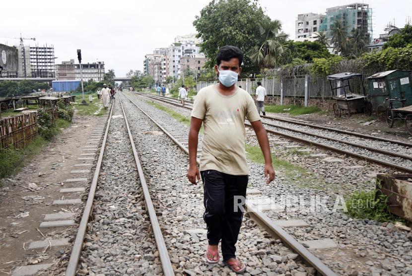 Seorang warga berjalan diatas rel kereta saat hari pertama pemberlakuan lockdown di Dhaka, Bangladesh, Senin (28/6). Pihak berwenang Bangladesh memberlakukan lockdown total secara nasional karena terjadinya peningkatan lonjakan kasus Covid-19. EPA-EFE/MONIRUL ALAMPutra M. Akbar