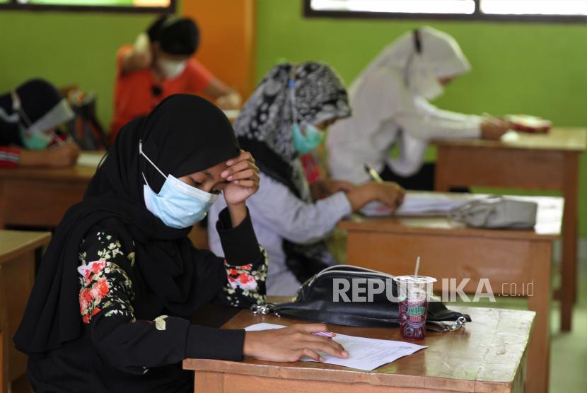 Sejumlah murid kelas 6 mengerjakan soal ujian semester  yang dilaksanakan secara tatap muka di SD Negeri 3 Kendari, Sulawesi Tenggara, Senin (5/4/2021). Seluruh Sekolah Dasar di Kendari melaksanakan ujian semester tatap muka perdana yang sebelumnya dilaksanakan secara virtual akibat pendemi COVID-19.