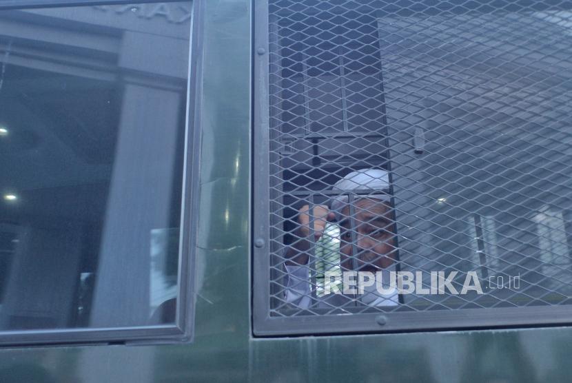 Terdakwa kasus dugaan pelanggaran karantina kesehatan Habib Rizieq Shihab (HRS) menaiki mobil tahanan usai menjalani sidang di Pengadilan Negeri Jakarta Timur, Jumat (26/3).