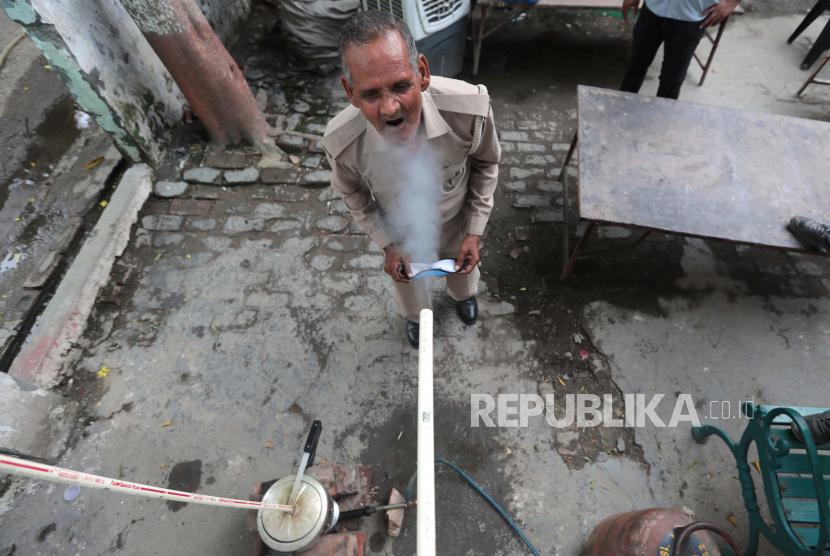 Personel polisi India menghirup uap herbal yang keluar dari pipa yang terhubung ke pressure cooker, sebagai tindakan pencegahan terhadap Covid-19 di luar kantor polisi di Ghaziabad, Uttar Pradesh, India, 03 Juni 2021.