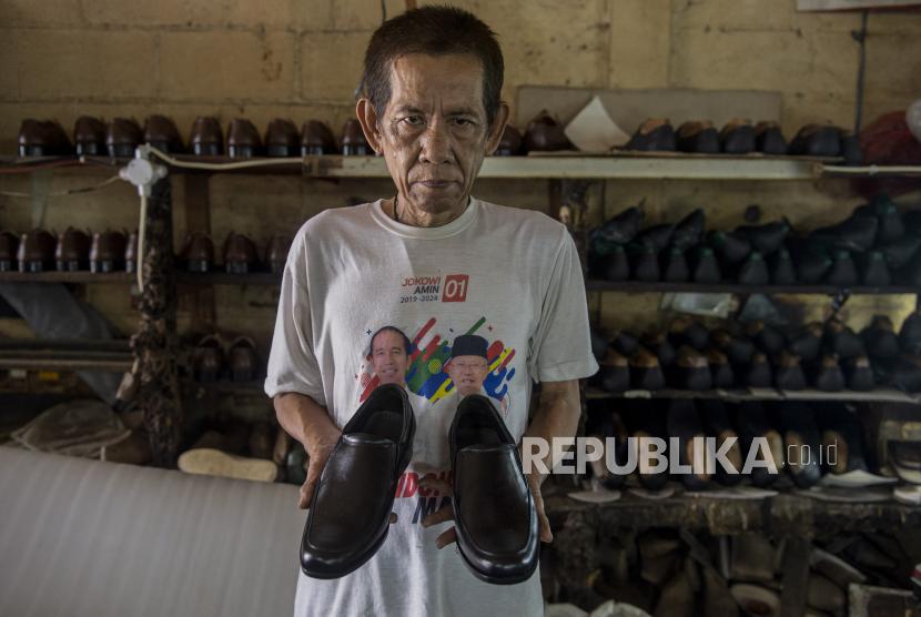 Pekerja menunjukkan sepatu yang telah jadi di bengkel kerja pembuatan sepatu milik Ardian di Perkampungan Industri Kecil (PIK) Penggilingan, Cakung, Jakarta Timur, Senin (2/8/2021). Adanya Pemberlakuan Pembatasan Kegiatan Masyarakat (PPKM) menyebabkan usahanya menurun hingga 70 persen dikarenakan toko-toko dan pusat perbelanjaan yang mengambil sepatu darinya tidak boleh berjualan.
