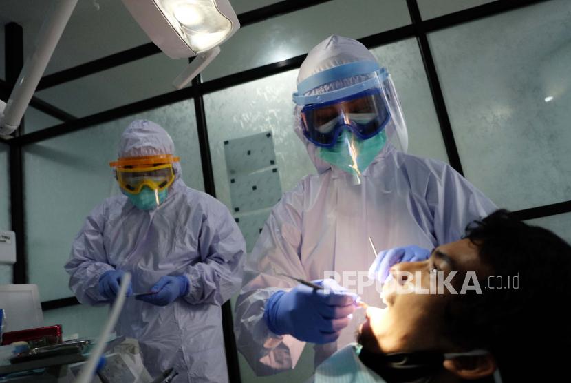 Dokter memakai alat pelindung diri (APD) level III (tiga) saat memeriksa kesehatan gigi pasien (ilustrasi).