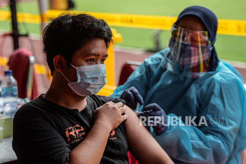 Tenaga kesehatan menyuntikan vaksin covid-19 Sinovac kepada warga saat vaksinasi massal di Bekasi.