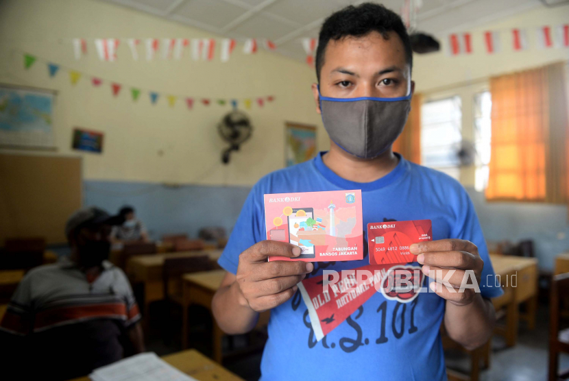 Warga menunjukan buku tabungan dan kartu debit usai mengambil Bantuan Sosial Tunai (BST). ilustrasi