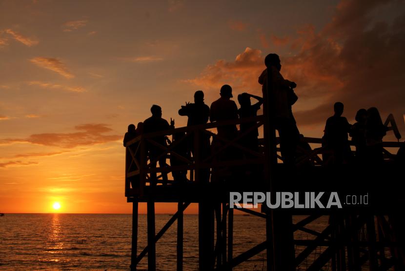 Asita Sulsel: Tes PCR Hambat Kunjungan Wisata. Pengunjung menikmati matahari tenggelam (sunset) di Ekowisata Mangrove Lantebung di Makassar, Sulawesi Selatan, Ahad (26/9/2021). Objek ekowisata tersebut mulai ramai dikunjungi wisatawan saat libur akhir pekan seiring penerapan Pemberlakuan Pembatasan Kegiatan Masyarakat (PPKM) di daerah itu turun level dari level 4 menjadi level 2 sebagai upaya penanganan COVID-19.