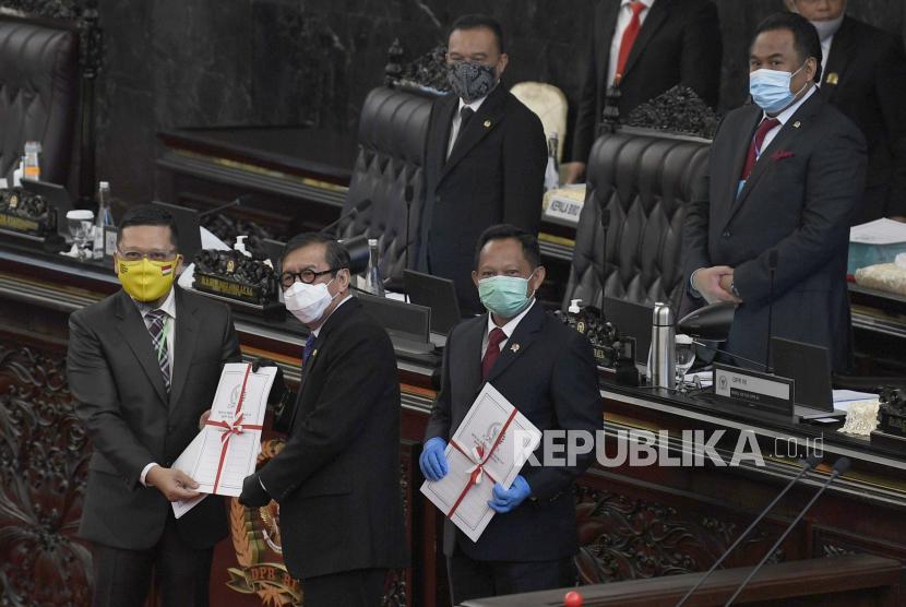 Ketua Komisi II DPR RI Ahmad Doli Kurnia Tanjung (kiri) menyerahkan dokumen UU Pilkada kepada Menteri Hukum dan HAM Yasonna Laoly (tengah) dan Mendagri Tito Karnavian (kanan) dalam Rapat Paripurna DPR ke-18 Masa Persidangan IV Tahun Sidang 2019-2020, di Kompleks Parlemen Senayan, Jakarta, Selasa (14/7/2020). DPR mengesahkan Rancangan Undang-Undang tentang Perppu Pilkada menjadi Undang-Undang. ANTARA FOTO/Puspa Perwitasari/hp.