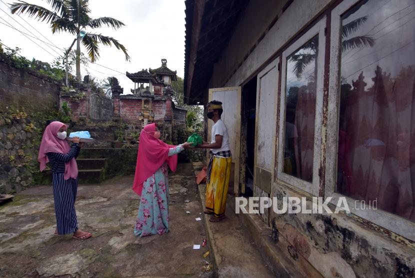 Umat Islam membagikan makanan kepada umat Hindu dalam Tradisi Ngejot di Banjar Tista, Desa Dapdap Putih, Buleleng, Bali, Rabu (12/5/2021). Tradisi yang digelar sehari sebelum perayaan Idul Fitri 1442 Hijriah tersebut untuk menjaga silaturahmi dan toleransi antar umat beragama.