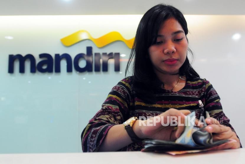 Petugas menghitung uang nasabah di Bank Mandiri.