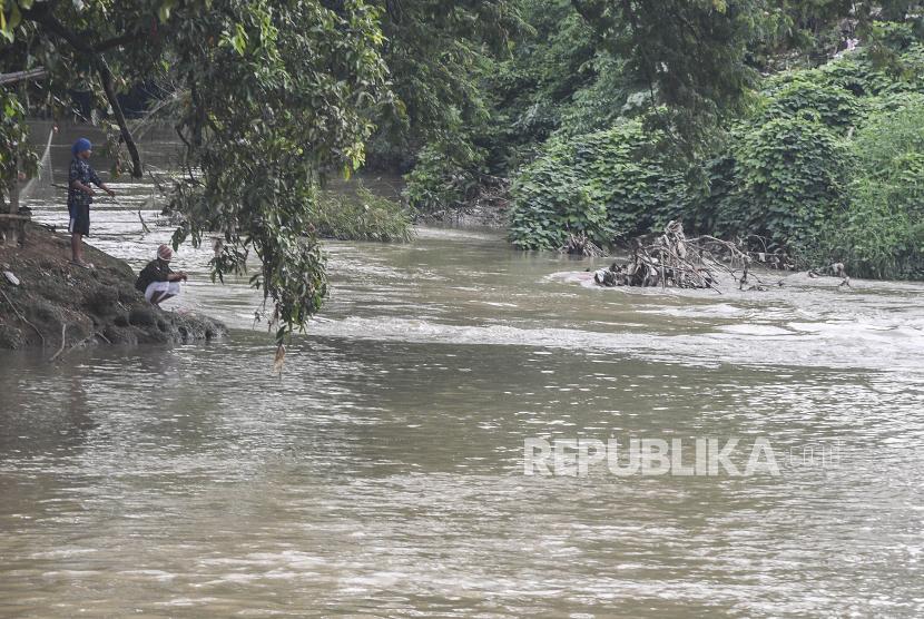 Sejumlah warga memancing ikan di aliran Kali Cikarang, Kabupaten Bekasi, Jawa Barat, Ahad (31/1/2021). Badan Penanggulangan Bencana Daerah (BPBD) Kabupaten Bekasi mengimbau warga yang tinggal di sekitar aliran kali untuk waspada banjir akibat kenaikan debit air Kali Cikarang karena curah hujan tinggi.