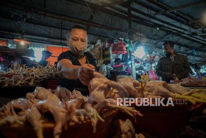 Pedagang daging ayam melayani pembeli.