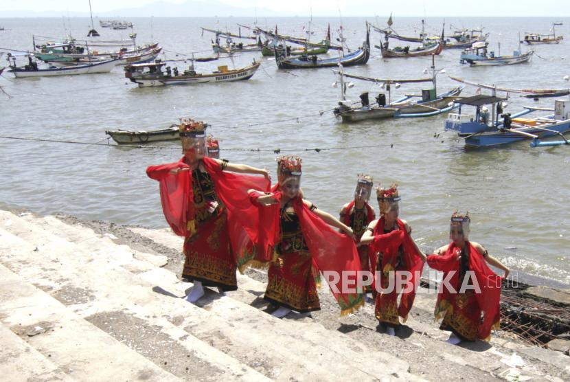 Penari menampilkan kreasi tari Larung Sesaji di tepi Pelabuham Satelit Muncar, Banyuwangi, Jawa Timur, Kamis (25/3/2021). Tarian yang ditampilkan oleh Padepokan Seni Dewi Sekartaji itu menceritakan nelayan muncar dalam melaksanakan tradisi petik laut sebagai warisan budaya leluhur.