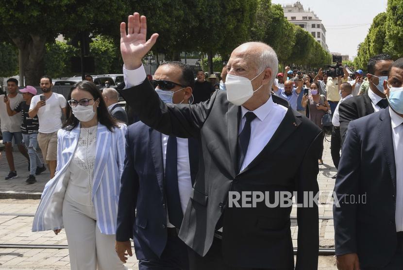 Presiden Tunisia Kais Saied melambai kepada para pengamat saat ia berjalan di sepanjang jalan Bourguiba di Tunis, Tunisia, Minggu, 1 Agustus 2021.