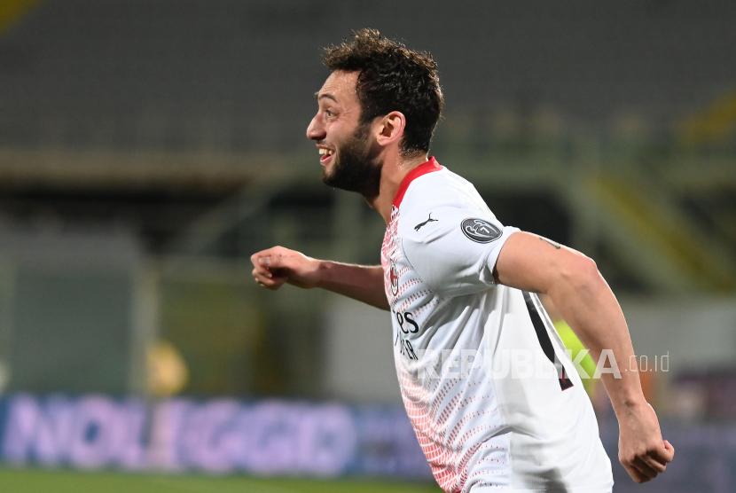 Gelandang Milan Hakan Calhanoglu melakukan selebrasi setelah mencetak gol ketiga timnya dalam pertandingan sepak bola Serie A Italia antara ACF Fiorentina dan AC Milan di stadion Artemio Franchi di Florence, Italia, Senin (22/3) dini hari WIB.