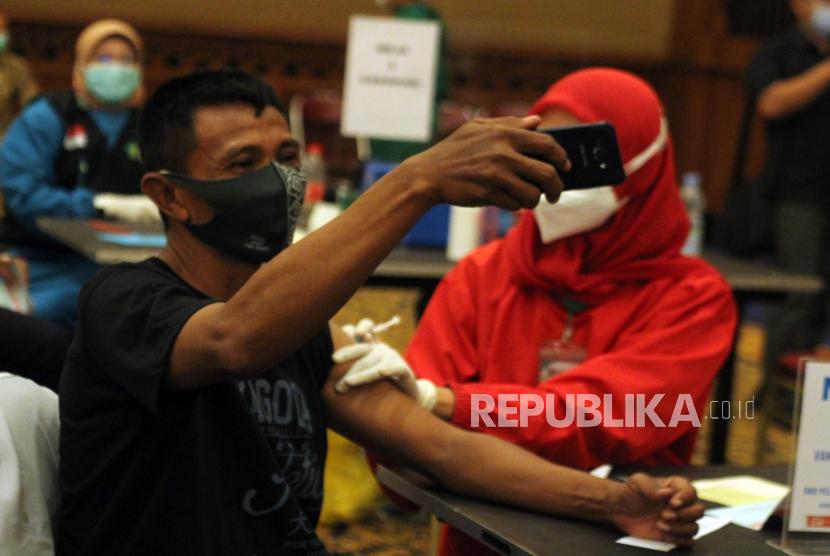 Anggota Dishub Kota Bogor berswafoto saat disuntikan vaksin COVID-19 di Kota Bogor, Jawa Barat, Selasa (2/3/2021). Menteri Kesehatan Budi Gunadi Sadikin mengatakan vaksinasi COVID-19 tahap kedua yang mencapai 38,5 juta orang dengan sasaran petugas pelayanan publik sebanyak 17 juta orang dan masyarakat berusia lanjut (lansia) sebanyak 21,5 juta orang tersebut akan rampung pada bulan Juni mendatang.